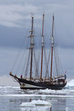 O navio de navigação preto do turista em águas antárticas obstruiu-se com Imagens de Stock