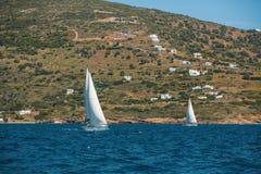 O navio de navigação yachts com as velas brancas no mar aberto imagem de stock