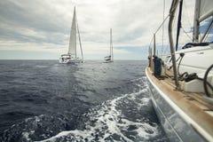 O navio de navigação yachts no mar no tempo nebuloso esporte imagens de stock