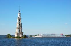 O navio de passageiro navega após a torre de sino do monastério no Rio Volga Kalyazin, Rússia fotos de stock