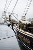 O navio do barco na água estacionou ao lado de um porto pequeno Foto de Stock Royalty Free