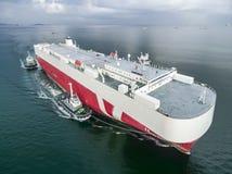 O navio do portador de carro do arrasto do barco de dois reboquees vai entrar Fotografia de Stock