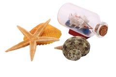 O navio na garrafa e na estrela do mar no fundo branco Imagem de Stock Royalty Free