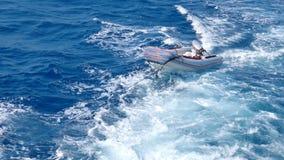 O navio reboca um bote atrás dele conectou por uma corda grossa filme