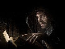 O necromante molda períodos do livro antigo grosso, atrás do vidro transparente coberto por gotas da água em um fundo escuro Fotos de Stock