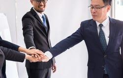 O negócio asiático junta-se ao sucesso das mãos para negociar, trabalho da equipe para conseguir objetivos, entrega a coordenação fotografia de stock royalty free