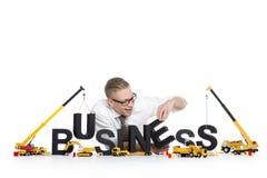 O negócio começa acima: Negócio-palavra da construção do homem de negócios. Fotos de Stock