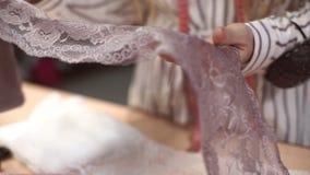 O negociante do tecido da loja substitui amostras de tecido no contador dentro filme