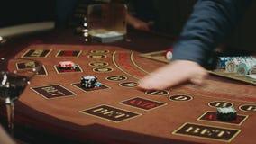 O negociante do vinte-e-um aceita a aposta e coloca cartões na tabela de jogo vídeos de arquivo