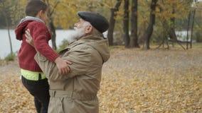 O neto feliz corre ao avô no parque do outono filme