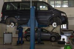 O ônibus, carro aumentou em um jaque hidráulico Reparo da suspensão, mudança do pneu fotografia de stock royalty free