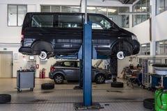 O ônibus, carro aumentou em um jaque hidráulico Reparo da suspensão, mudança do pneu Imagens de Stock Royalty Free