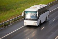 O ônibus de turista vai na estrada do país Imagens de Stock