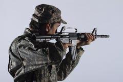 Żołnierz bierze cel z karabinem szturmowym, horyzontalnym obrazy royalty free