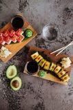 O nigiri do sushi e os rolos de sushi ajustados com chá serviram na ardósia de pedra cinzenta fotografia de stock royalty free