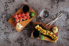 O nigiri do sushi e os rolos de sushi ajustados com chá serviram na ardósia de pedra cinzenta foto de stock