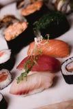 O nigiri e os rolos do sushi do close up serviram na tabela de madeira marrom na placa Alimento asiático saudável Fotografia macr Imagens de Stock