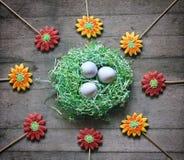 O ninho de papel com os ovos cercados pelo pão-de-espécie colorido floresce Fotografia de Stock