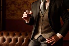 O noivo à moda realiza em sua mão um o vidro do uísque imagens de stock royalty free