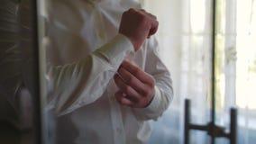 O noivo abraça as luvas em uma camisa em casa vídeos de arquivo