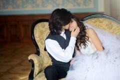O noivo abraça e acaricia a noiva que senta-se em um sofá bonito em um interior antigo fotografia de stock royalty free