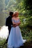 O noivo abraça a noiva em um parque romântico pela água Caminhada Wedding imagens de stock royalty free