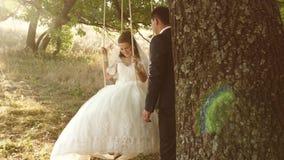 O noivo agita sua noiva no balanço e nos sorrisos com olhar de amor A mulher e o homem na reunião romântica estão felizes nos des vídeos de arquivo