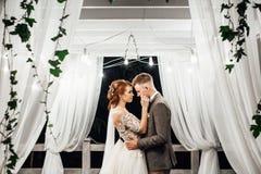 O noivo beija o mordente do ` s da noiva macio abraçando a no jardim fotos de stock