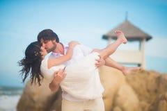 O noivo beija uma noiva bonita em suas mãos contra as rochas, o mar e o céu imagens de stock royalty free