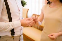 O noivo coloca a aliança de casamento sobre o fim da noiva A noiva põe o noivo sobre a aliança de casamento imagem de stock