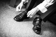 O noivo concorda sapatas com o dia do casamento Fotos de Stock Royalty Free