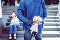 O noivo considerável está escondendo o ramalhete da flor atrás do seu para trás imagem de stock