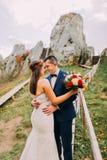 O noivo considerável no terno azul à moda que abraça delicadamente seu branco vestiu a noiva que guarda o ramalhete das rosas em  imagens de stock
