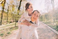 O noivo de sorriso leva sua noiva loura bonita sobre para trás fora no parque da mola Foto de Stock