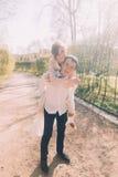 O noivo de sorriso leva sua noiva loura bonita sobre para trás fora no parque da mola Foto de Stock Royalty Free