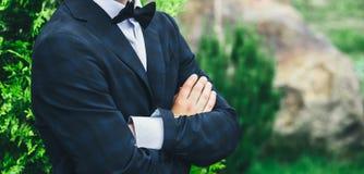 O noivo do close up em um terno azul, em uma camisa branca e em uns braços da borboleta do laço cruzou-se contra um fundo de um a Fotografia de Stock