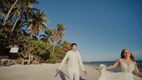 O noivo e a noiva bonita correm com os pés descalços ao longo da costa arenosa do oceano feliz junto Um casamento tropical filme