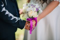 o noivo e a noiva guardam o ramalhete do casamento fotografia de stock