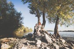 O noivo e a noiva no banco de rio Fotografia de Stock Royalty Free