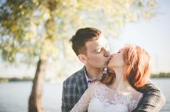 O noivo e a noiva no banco de rio Imagens de Stock Royalty Free