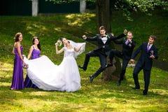 O noivo e os groomsmen saltam atrás das senhoras bonitas Fotografia de Stock Royalty Free