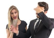 O noivo embaraçado mostra a tela do telefone celular a seu girlfri foto de stock royalty free