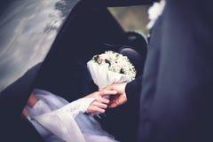O noivo encontra a noiva do carro com o ramalhete do casamento das flores Fotografia de Stock