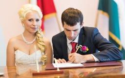 O noivo escreve no registro da união fotos de stock royalty free