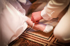 O noivo está ajudando a desgastar em sapatas de um branco da noiva imagens de stock royalty free