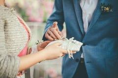 O noivo está tomando a aliança de casamento no terno para vesti-lo à noiva foto de stock