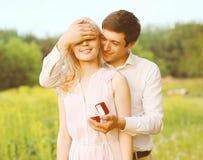 O noivo fechado o seu eyes uma menina, fazendo um anel da surpresa Imagem de Stock Royalty Free