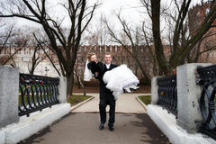 O noivo feliz carreg sua noiva em seus braços fotografia de stock