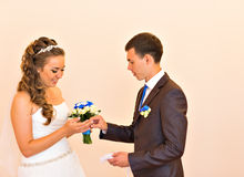 O noivo feliz veste a aliança de casamento sua noiva Registo solene da união fotos de stock royalty free