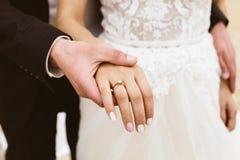 O noivo guarda a mão do ` s da noiva imagens de stock royalty free